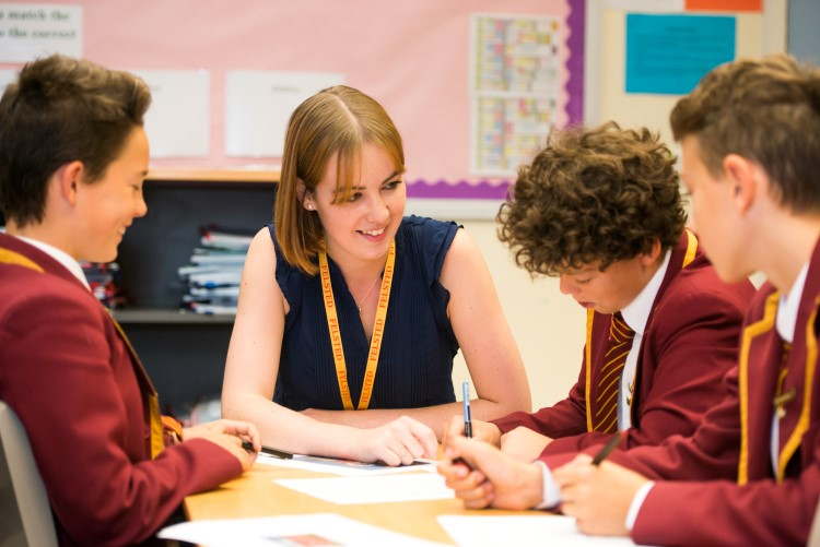 A female teacher sits with three Felsted boys in a classroom