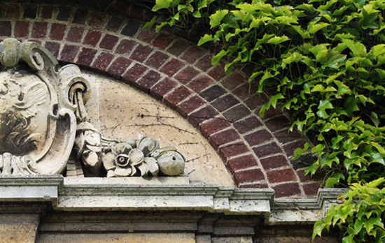 Architectural wall decoration with a stone brick arch and ivy