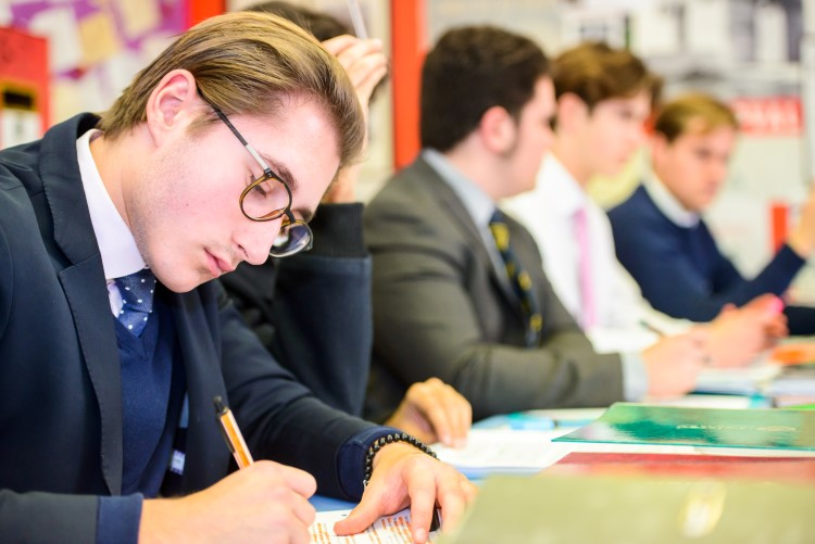 A Felsted Sixth-Former takes notes during a lesson in a classroom