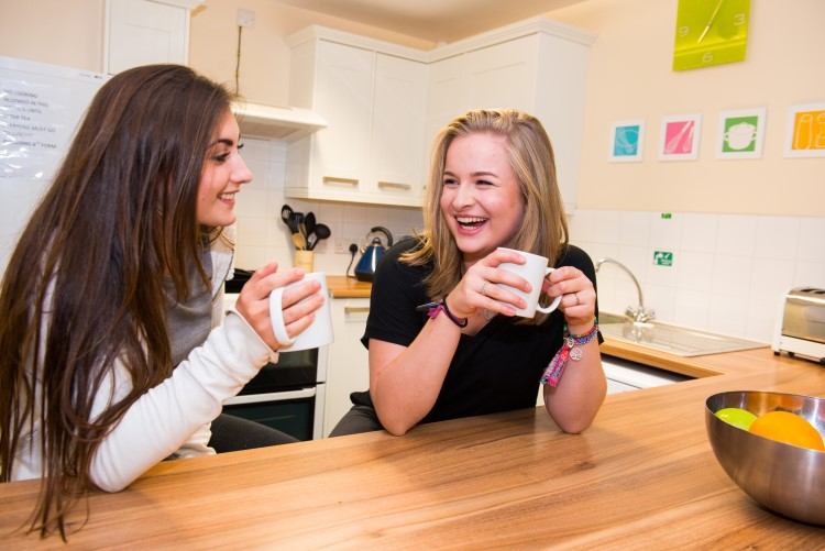 Two Sixth-Form Boarders talk over a hot drink in a kitchen