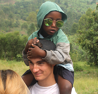 A student with a young boy on his shoulders