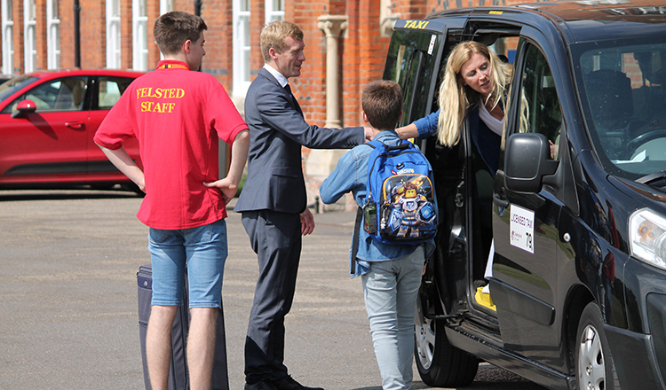 Felsted staff greeting summer school students from a taxi
