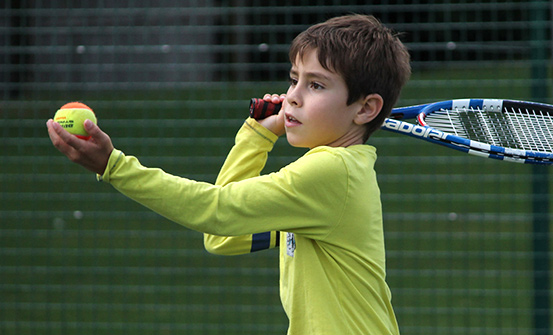 A young boy about to serve a tennis ball