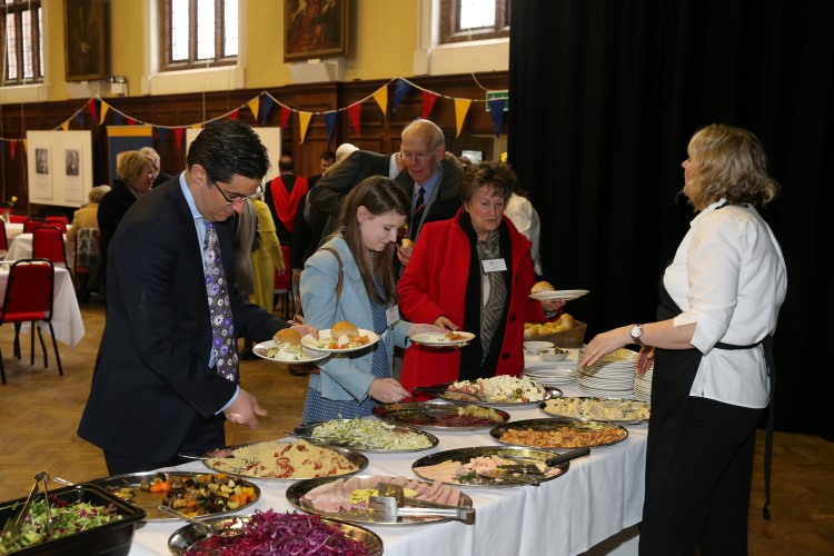 Several attendees pick food from a buffet